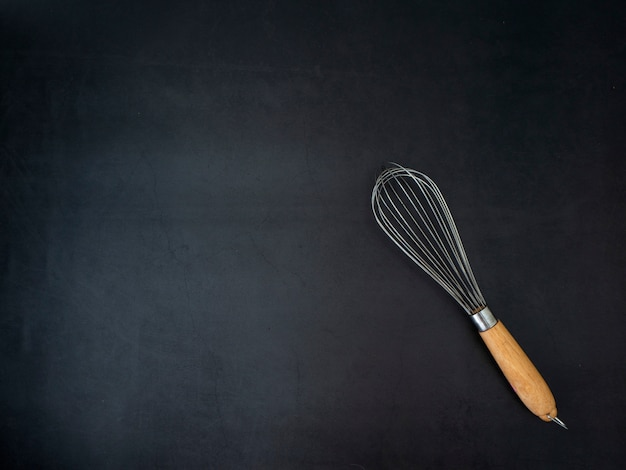 Wire whisk dark granite board background Premium Photo
