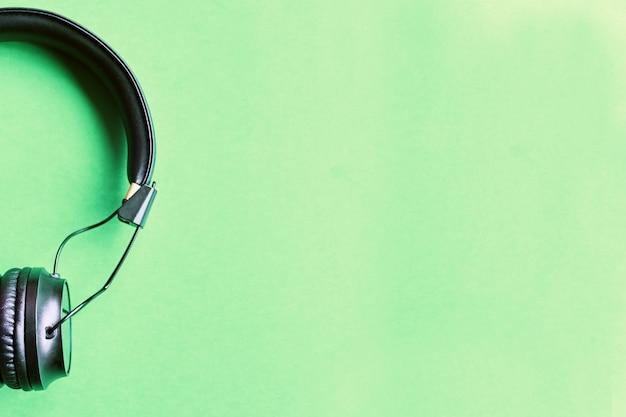 Wireless black headphones on colorful green background Premium Photo