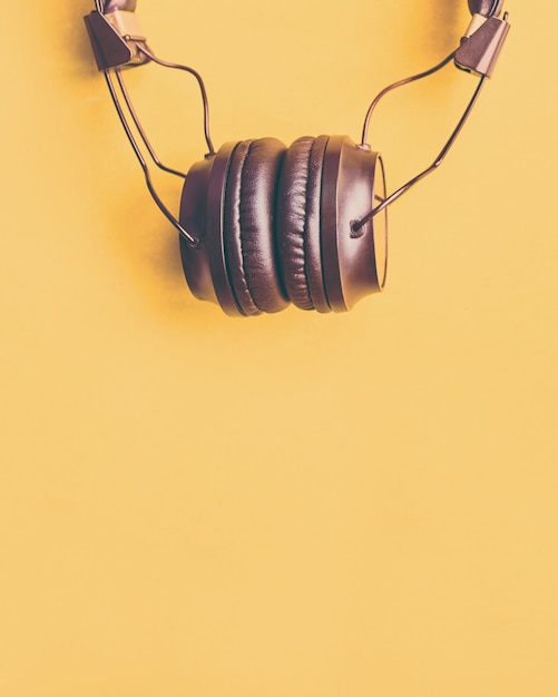Wireless black headphones on colorful yellow background Premium Photo
