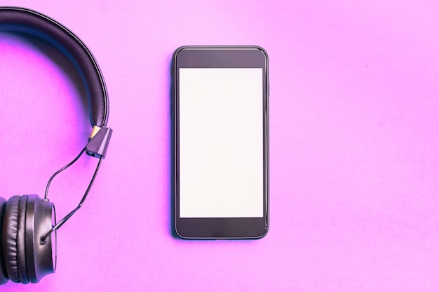 Wireless headphones and smartphone on colorful pink background Premium Photo