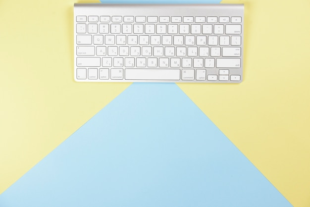 Wireless white keyboard on yellow and blue background Free Photo