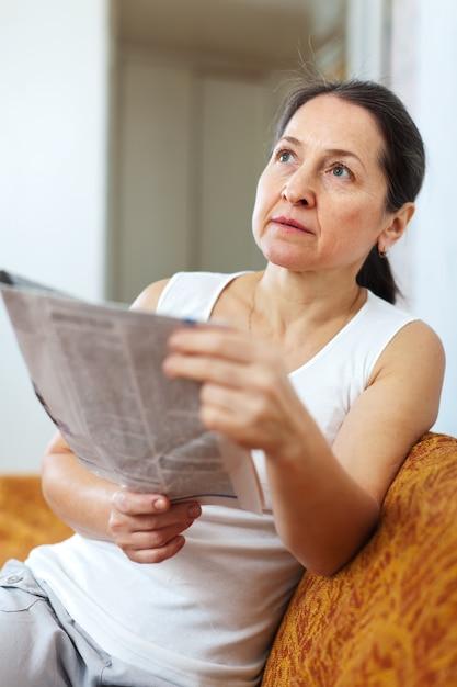 Wistful  woman with newspaper Free Photo