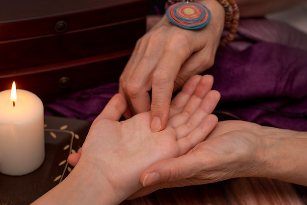 Witch fortune teller reading fortune on girls hand. Premium Photo