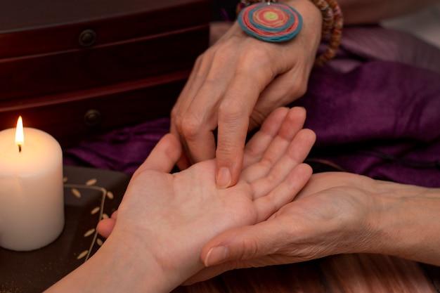 Гадалка ведьмы читая удачу на руке девушки. Premium Фотографии