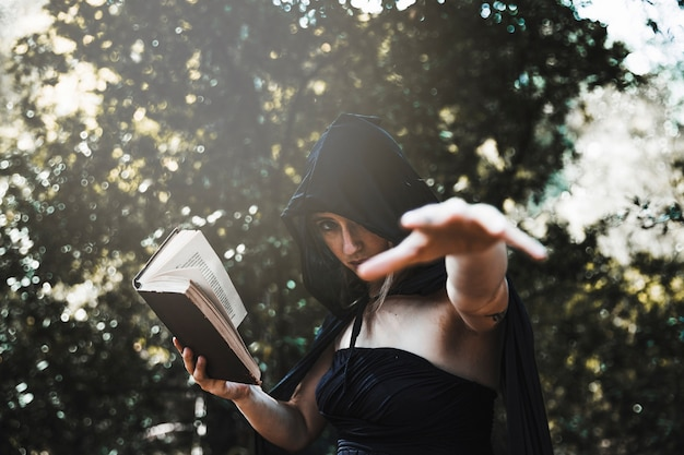 Witch with spellbookusing magic in sunlitwoods Free Photo