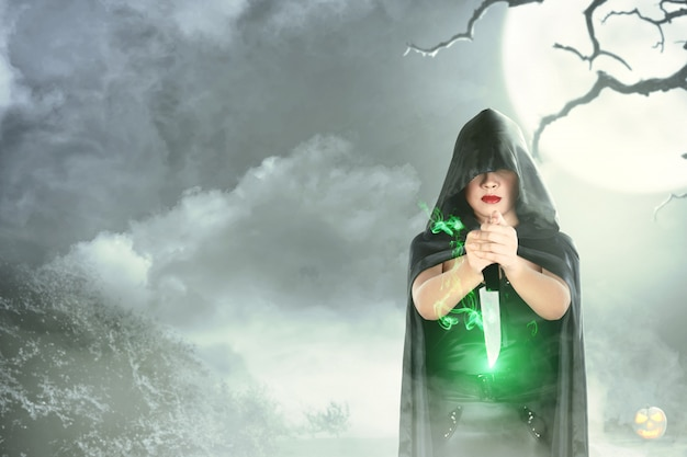Witch woman in black hooded doing ritual magic with a knife Premium Photo