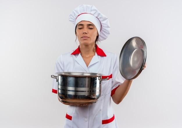 目を閉じて、コピースペースで鍋と蓋を保持しているシェフの制服を着た若い女性料理 無料写真