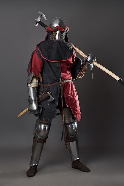 灰色の中世の騎士。チェーンメールの鎧の赤と黒の服と戦いのwithを持つ残忍な汚い顔の戦士の肖像画 Premium写真