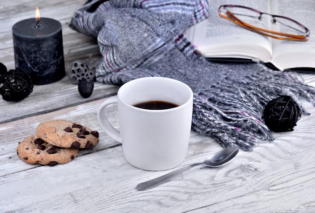 コーヒーwithscarfと白いテーブルの上のキャンドルのマグカップ Premium写真