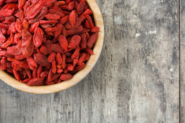 Wolfberries or goji berries in bowl on wooden surface top view Premium Photo