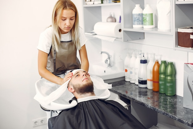 Woma washing man's head in a barbershop Free Photo