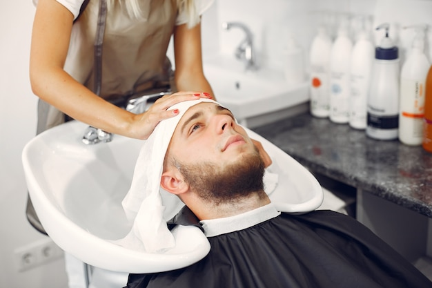 Woma washing man's head in a barbershop Free Photo