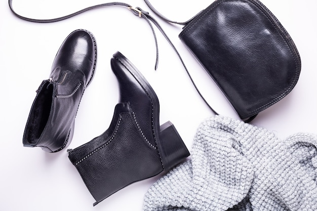 Woman accessory. black stylish boots, black luxury leather bag, gray scarf. top view. flat lay. Premium Photo
