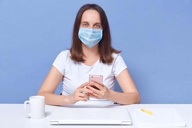 自宅で仕事をしている女性会計士、防護マスクを着用、コロナウイルスの隔離中にリモートで仕事をしている女性モデレーター Premium写真