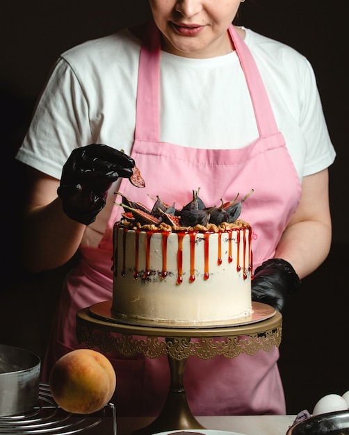 Woman adding fig piece on classic cake decorated with figs and syrup Free Photo