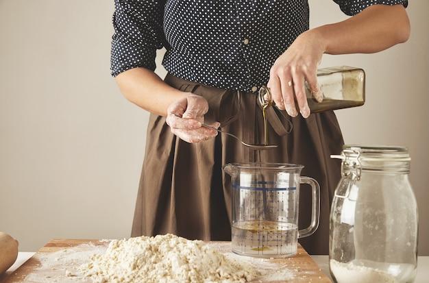 La donna aggiunge un po 'di olio d'oliva in acqua nella tazza di misura dietro il tavolo con gli ingredienti della pasta, per fare la pasta o gli gnocchi processo di presentazione della cottura Foto Gratuite