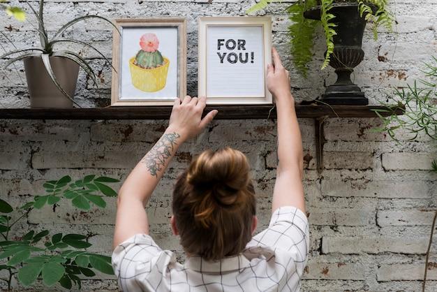 Woman adjusting for you photo frame on shelf Premium Photo