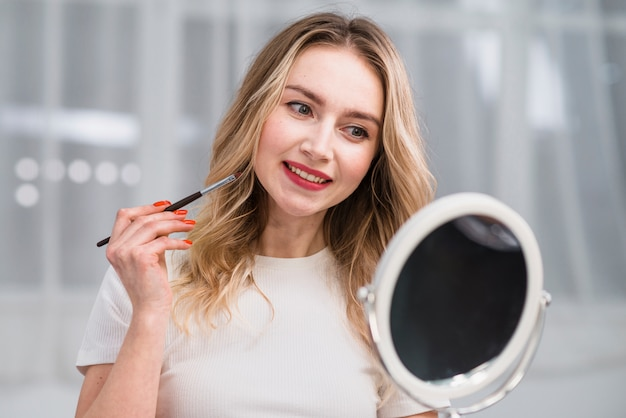 Woman admiring makeup of lips in mirror Free Photo