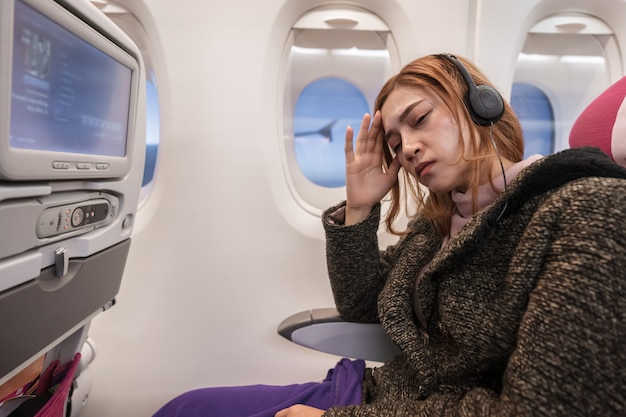 Woman in airplane suffer from airsick with stress headache in flight time. Premium Photo