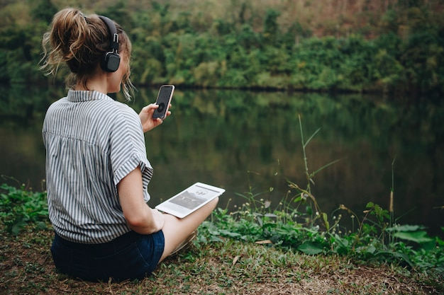 Woman alone in nature listening to music with headphones, digital tablet and a smartphone music and Premium Photo