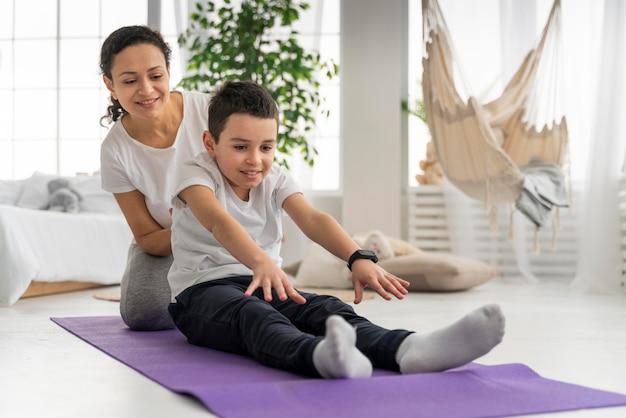 Женщина и мальчик на коврике для йоги полный кадр Бесплатные Фотографии