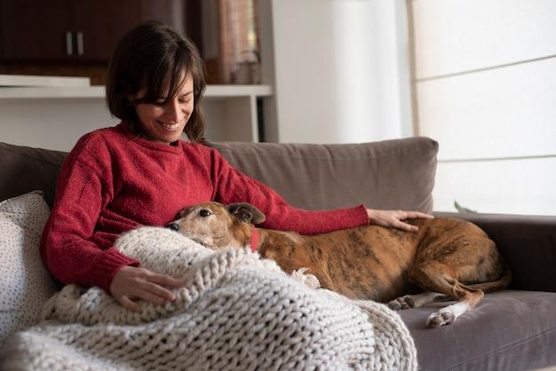 Женщина и собака, отдыхая на диване Premium Фотографии