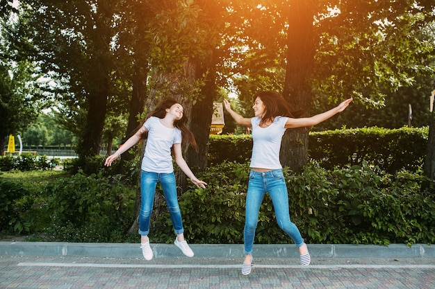 Woman and girl jumping on pavement Free Photo
