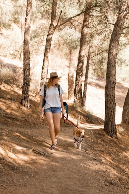 Женщина и ее собака гуляют в лесу Premium Фотографии