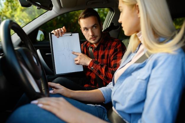 車と自動車学校のチェックリストを持つ女性とインストラクター。車を運転する女性を教える男。 Premium写真