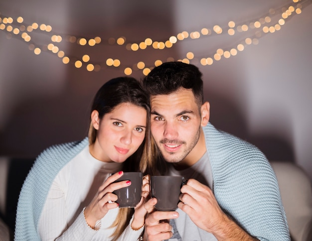 Woman and man in coverlet with mugs on sofa in dark room Free Photo