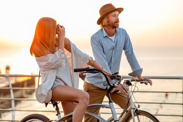 女と夕日の海で自転車に乗って愛の男 無料写真