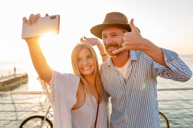 Женщина и мужчина в любви, путешествующие на велосипедах на закате моря Бесплатные Фотографии