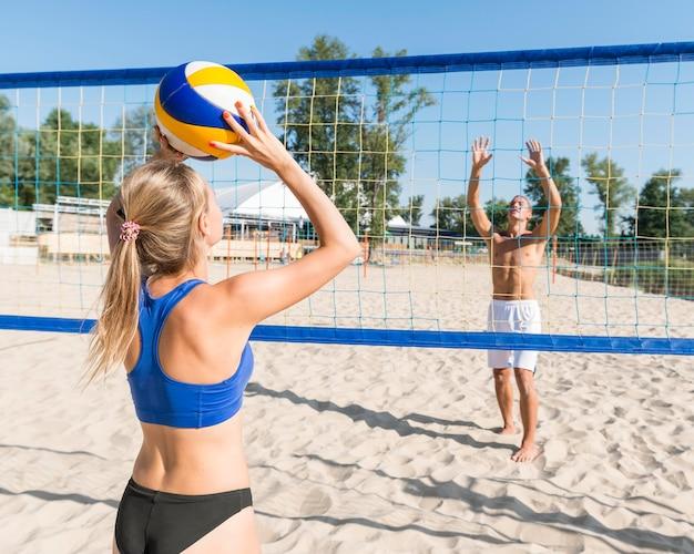 女と男が一緒にビーチバレーボールを再生 無料写真