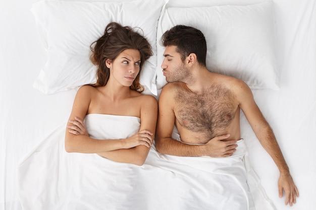 Женщина и мужчина, сидя в постели, вид сверху Бесплатные Фотографии