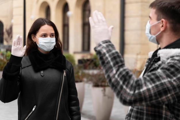 Женщина и мужчина машут альтернативными приветствиями на открытом воздухе Бесплатные Фотографии