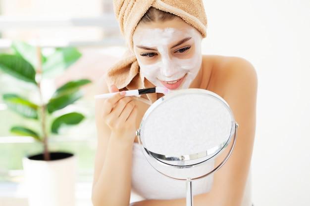 女性はホテルの豪華なバスルームで顔のスキンケアに白い粘土のマスクを適用します Premium写真
