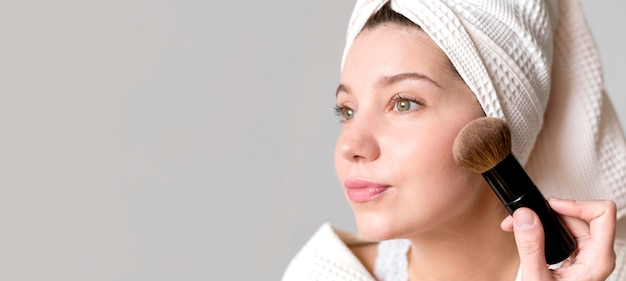 Woman applying blush with copy-space Free Photo