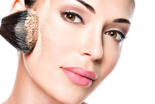 Donna che applica il fondotinta tonale cosmetico secco sul viso utilizzando il pennello per il trucco. Foto Gratuite