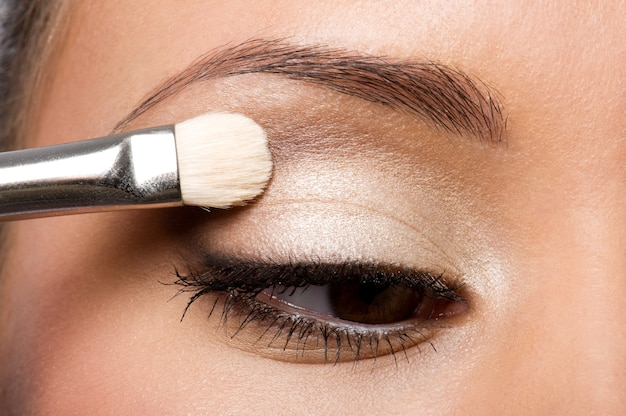 Woman applying eyeshadow on eyelid using makeup brush Free Photo
