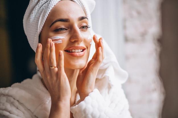 Woman applying face cream Free Photo