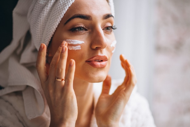 Woman applying face cream Free Photo