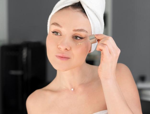 Woman applying face serum Free Photo