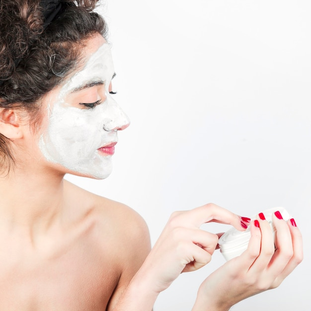 Woman applying facial mask on her face against white background Free Photo
