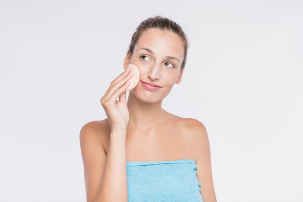 Woman applying facial sponge Free Photo