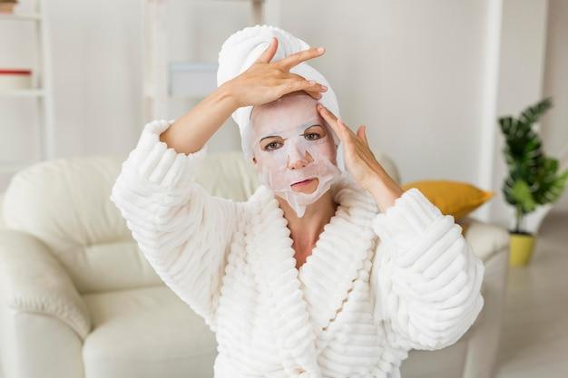 Женщина, применяющая среднюю маску для лица Бесплатные Фотографии