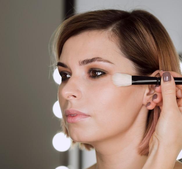 Woman applying highlighter on model Free Photo