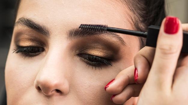 Woman applying make up on model Free Photo