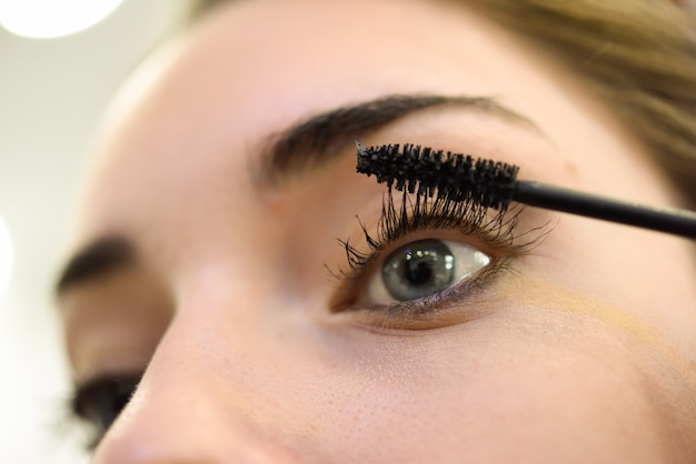 Woman applying makeup eyelashes Free Photo