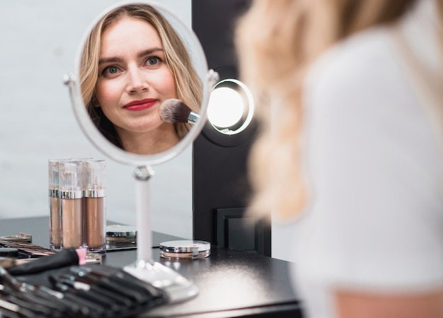 Woman applying makeup reflecting in mirror Free Photo
