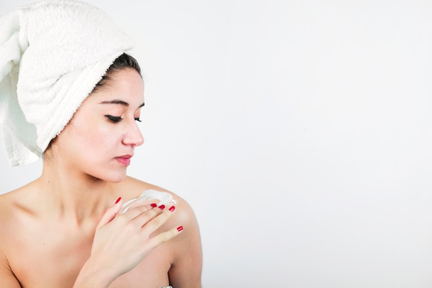 Woman applying moisturizer to her shoulder against white background Free Photo